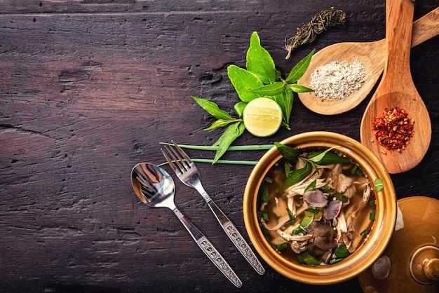 Hete groentesoep met kip, puree, kruiden, pompoenpitten voor lunchfilet in een kom op donkere rustieke houten achtergrond bovenaanzicht