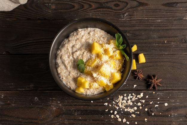 Hete havermout met verse mangostukjes, gekookt in melk en gegarneerd met munt cantharellen.