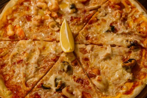 Hete heerlijke pizza met gesmolten kaas en zeevruchten op een rustieke houten tafel. zeevruchten pizza op een houten dienblad