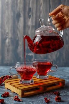 Hete hibiscus thee in een glazen mok en glazen theepot.