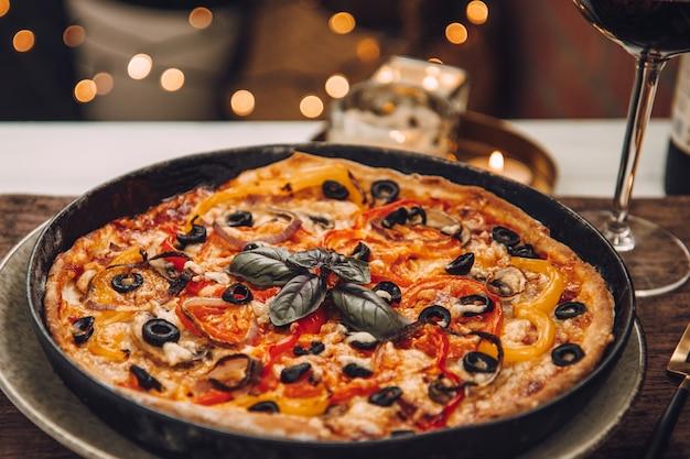 Hete italiaanse pizza voor het avondeten met een glas rode wijn. romantische avond