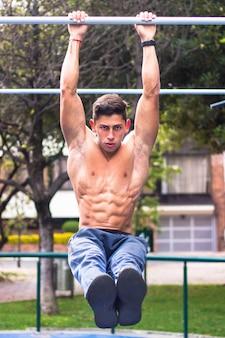 Hete jonge gespierde man aan het trainen op horizontale balken horizontal