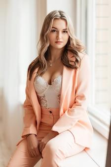 Hete jonge stijlvolle vrouw in modieus pak en blazer met witte sexy kanten bodysuit-lingerie die binnenshuis bij het raam zit