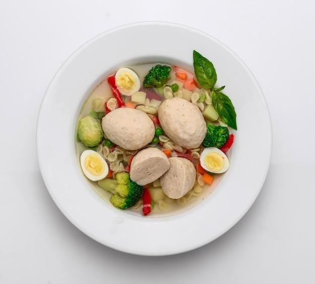 Hete kippensoep, bouillon met gehaktballetjes, wortel, pasta en verse peterselie