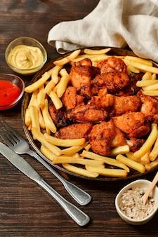 Hete kippenvleugels en frieten met ketchup en mosterd.