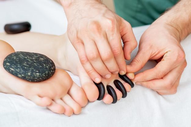Hete kleine zwarte steentjes tussen de vrouwelijke tenen