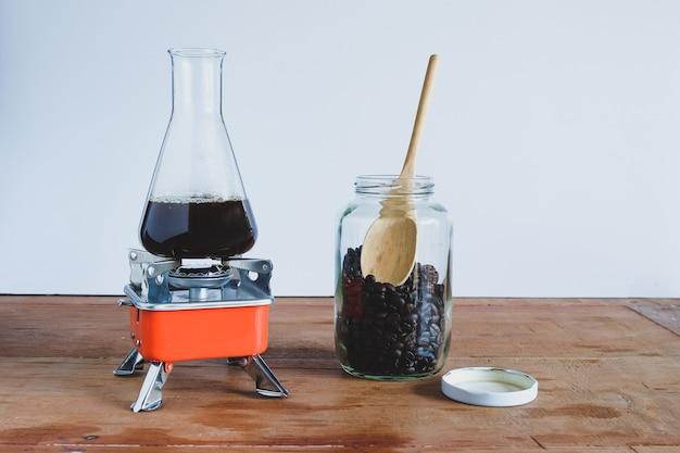 Hete koffie brouwen in laboratoriumbuis op kampeerfornuis.