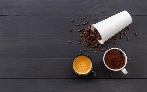 Hete koffie en bonen op zwart hout