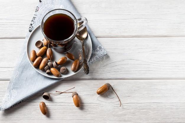 Hete koffie gemaakt van eikels in een glas is een tonische drank met een koffiesmaak, een rijke kleur en een aangenaam aroma.