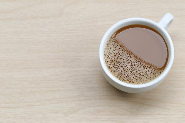 Hete koffie in een witte koffiekop op houten lijst.