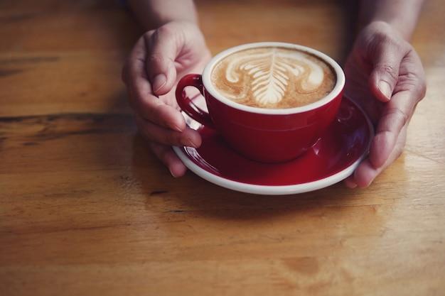 Hete koffie latte cappuccino in rode kop en schotel met het mooie melkschuim van de lattekunst op de handen die van de barista het dienen op houten lijstachtergrond houden.