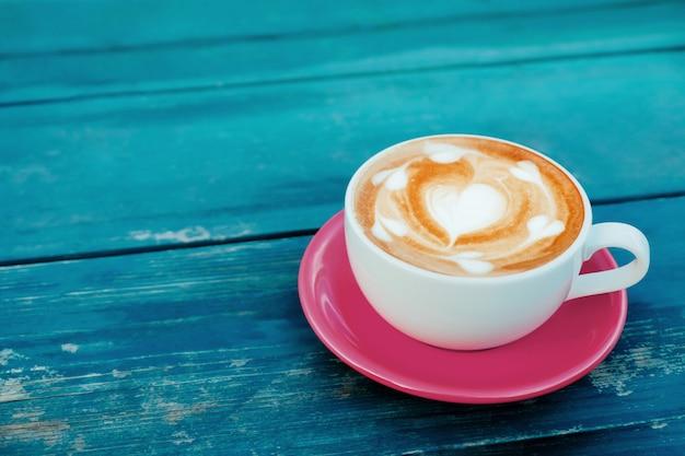 Hete koffie latte cup op houten tafel met kopie ruimte. bovenaanzicht