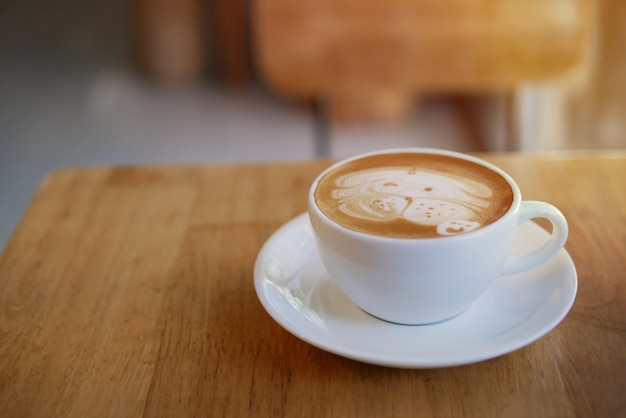 Hete koffie latte kop met schattige pug dog latte kunst melkschuim op lichte houten tafel met ochtendzonlicht in ontspannende coffeeshop achtergrond.