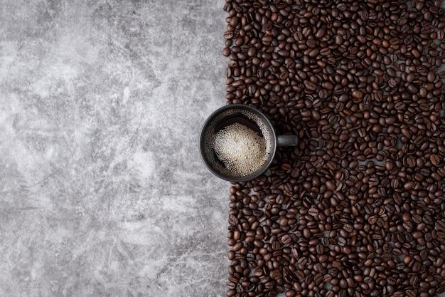 Hete koffiekop met koffiebonen op de achtergrond van de cementmuur.