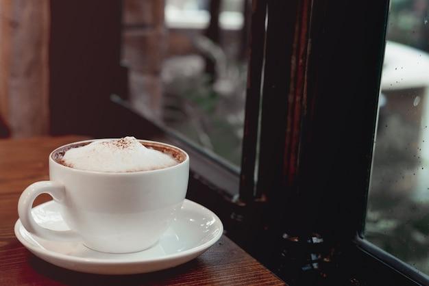 Hete koffiekop op een achtergrond van het rainny dagvenster