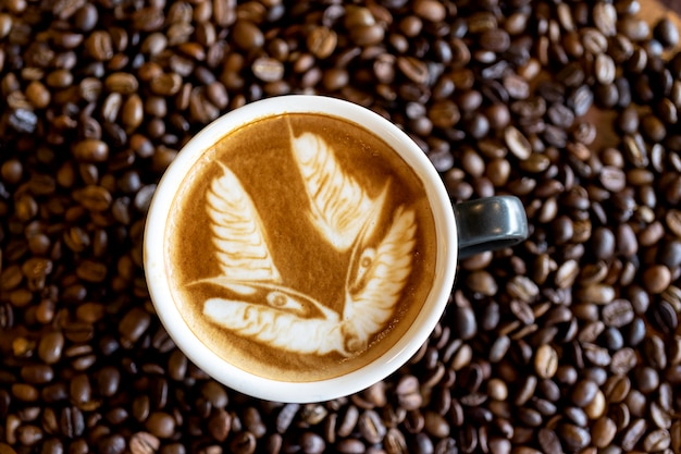 Hete kunstkoffie latte kunst in een kop op de achtergrond van de koffieboon