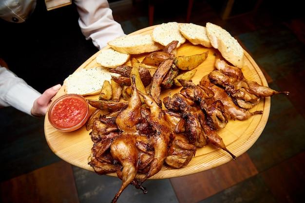 Hete kwartels grillen met saus en croutons op een houten bord in de handen van een ober