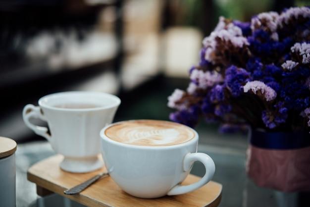 Hete latte kunst in koffiekop op houten lijst in koffiewinkel