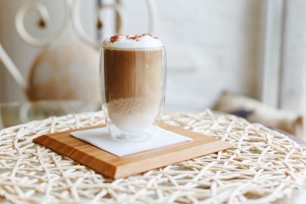 Hete latte of cappuccino-koffie op een lijst in koffie dichtbij venster met exemplaarruimte.