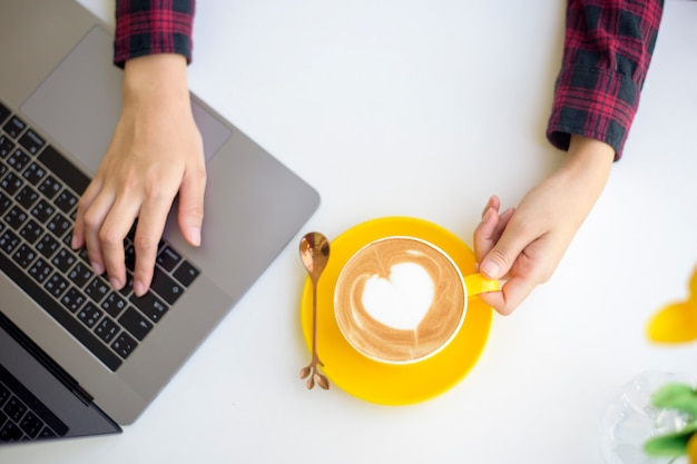 Hete lattekunst in gele kop op bureau