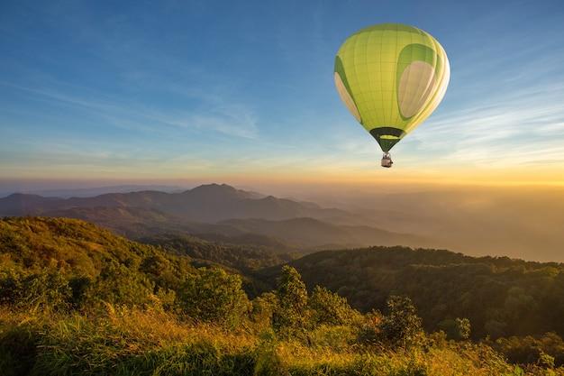 Hete luchtballon boven hoge berg bij zonsondergang