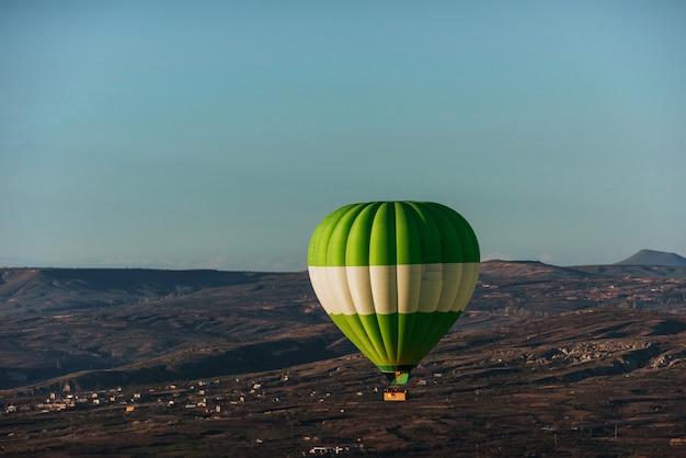Hete luchtballon boven hoge berg