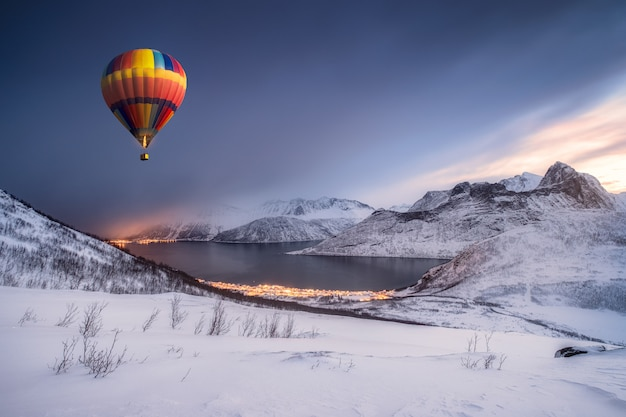 Hete luchtballon die op sneeuwheuvel vliegen met fordgard stad in de winter
