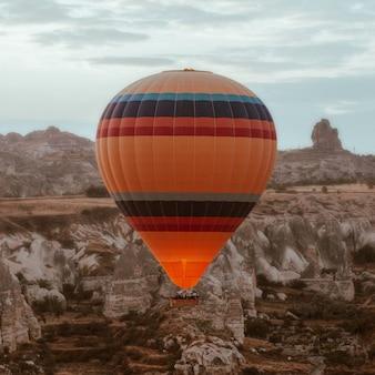 Hete luchtballon die over cappadocia bij dageraad vliegt