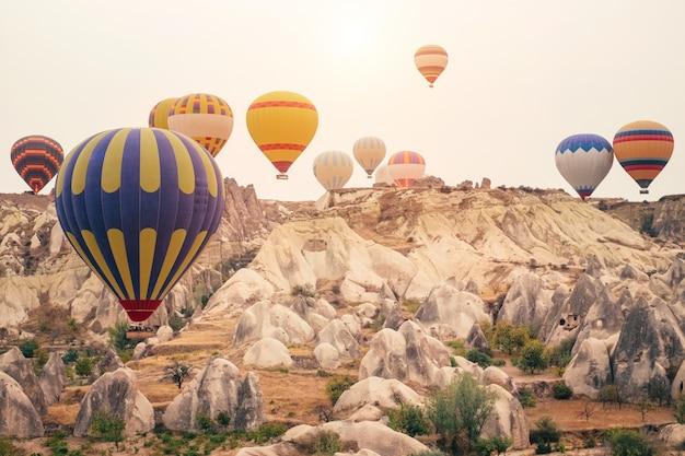 Hete luchtballon die over het berglandschap van cappadocia bij gouden zonsopgang vliegt