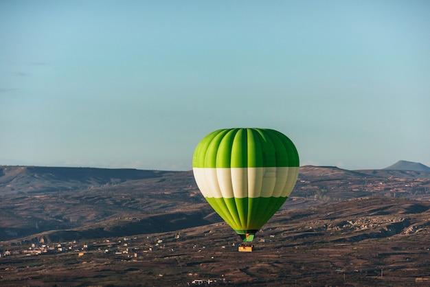 Hete luchtballon die over rotslandschap in cappadocia turkije vliegt. vallei, ravijn, heuvels, gelegen tussen de vulkanische bergen