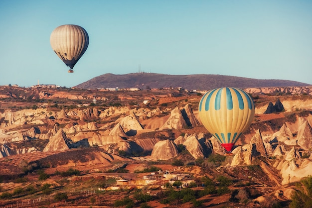Hete luchtballon die over rotslandschap in cappadocia turkije vliegt.