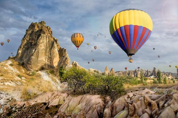 Hete luchtballon die over rotslandschap in cappadocia turkije vliegt