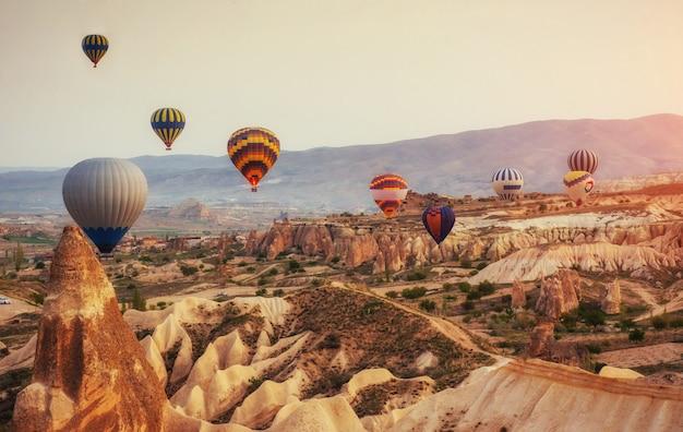 Hete luchtballon die over rotslandschap in turkije vliegt. cappadocië