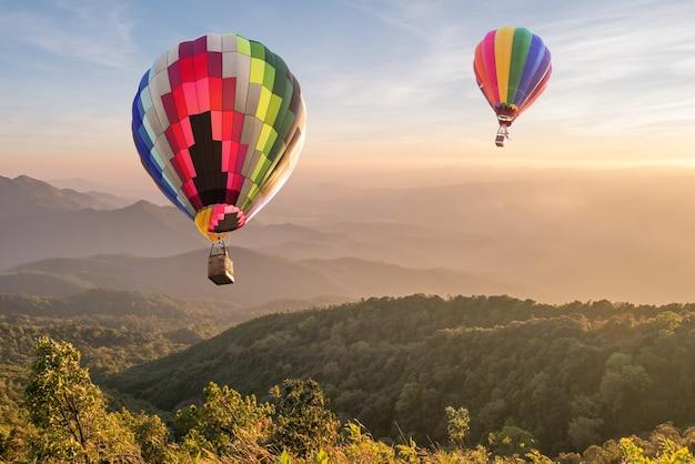 Hete luchtballon over berg bij zonsondergang