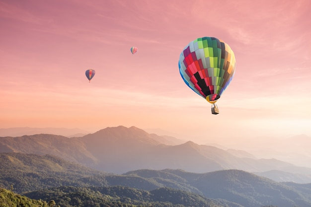 Hete luchtballon over hoge berg bij zonsondergang