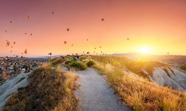Hete luchtballons die over een stad vliegen