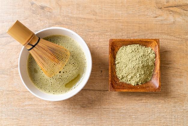 Hete matcha groene theekop met groene theepoeder en garde