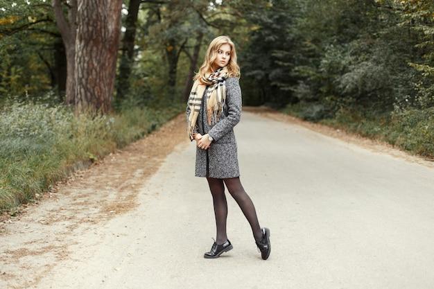 Hete modelvrouw in vintage warme sjaal in een jas en schoenen die op de weg in het park lopen.
