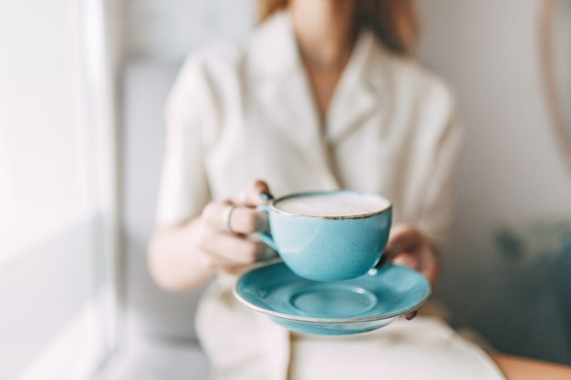 Hete mok koffie in de handen van een jong meisje. sfeervolle coffeeshop en stijlvolle gerechten.
