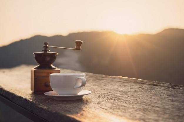Hete ochtendkop van koffie met bergenachtergrond bij zonsopgang met exemplaarruimte