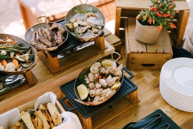 Hete pannen met gekookt voedsel op een gietijzeren fornuis op een houten tafel met een bosje bittere peper