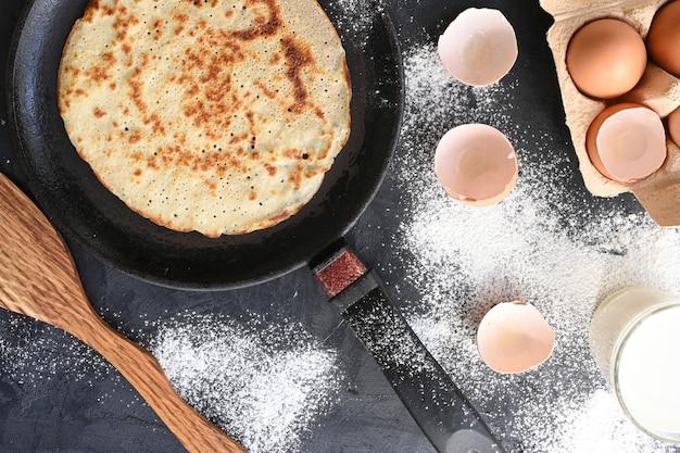 Hete pannenkoek in zwarte pan op zwarte tafel met bloem, melk en eieren.