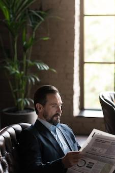 Hete pers. leuke knappe aantrekkelijke zakenman die een krant vasthoudt en deze leest terwijl hij op de leren bank zit