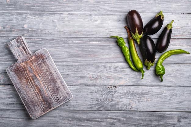 Hete pittige groene chili peper en verse rijpe auberginegroenten met oude snijplank