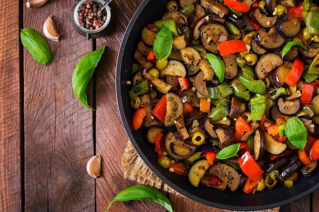 Hete pittige stoofpot aubergine, paprika, olijven en kappertjes met basilicum bladeren. bovenaanzicht