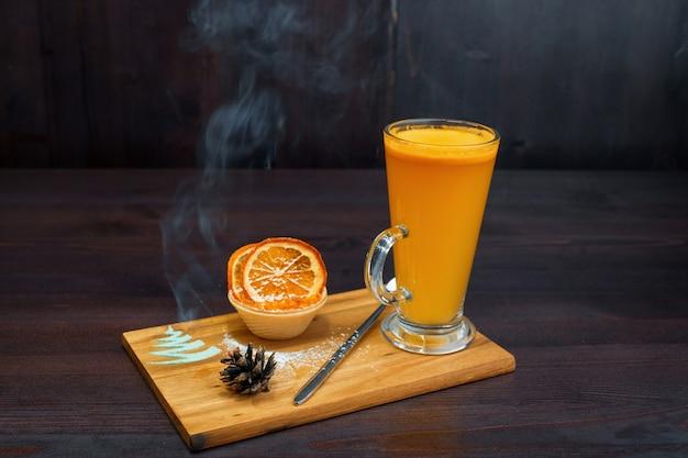 Hete pittige theedrank van gele kleur met jam met plakjes gedroogde sinaasappel staat op tafel