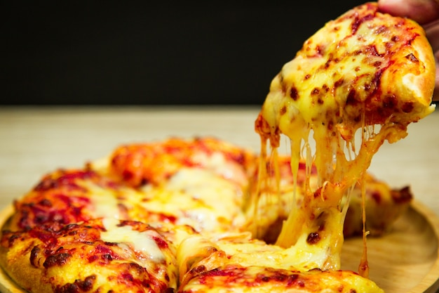Hete pizzaplak met smeltende kaas op een lijst in restaurantpizza.