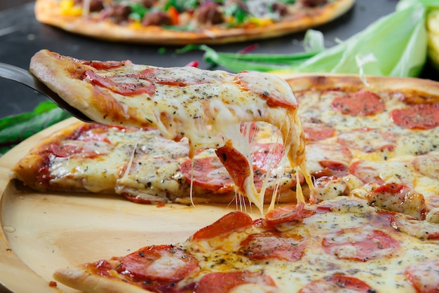 Hete pizzapunt met smeltende kaas op een rustieke donkere houten tafel.