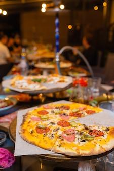 Hete pizzapunt met smeltende kaas op een rustieke houten tafel.