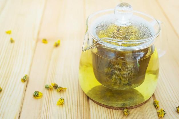 Hete pot van chrysanthemum klaar om te drinken op houten tafel